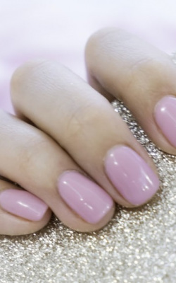 Close up pink nails for girls. Stylish trendy female manicured fingernails. Beautiful young woman's hands on pink and blue background. Top view, flat lay. copy space for text